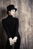 pic of mime  - Elegant expressive male mime artist posing with walking stick by a grunge wall - JPG