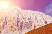 stock photo of mountain-climber  - climbers at the top of a pass with backpacks meeting the sunrise in the mountains - JPG