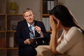 picture of nervous breakdown  - Mature psychiatrist and his crying patient in the office - JPG