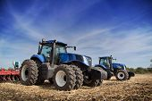 image of tractor  - Two blue tractor with drills in the field under blue sky - JPG