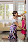 stock photo of measuring height  - Mother measuring height of her little daughter - JPG