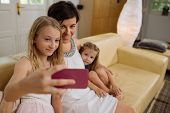 image of little sister  - Preteen girl taking selfie with her mother and little sister - JPG