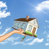foto of women rights  - House and keys in right womans hand on blue sky background - JPG