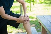 pic of pain-tree  - Closeup cropped portrait man in black shirt and shorts holding knee in severe pain isolated trees and picnic bench outside background - JPG