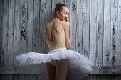 stock photo of tutu  - Modest ballerina standing near a wooden wall on pointe in a tutu - JPG