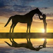 image of horse girl  - Silhouette of a girl giving a kiss horse in sunset - JPG