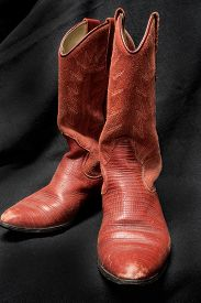 image of cowgirl  - A photo of a pair of red leather cowgirl boots on a black background - JPG