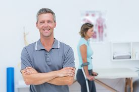 stock photo of crutch  - Doctor smiling at camera while his patient standing with crutch in medical office - JPG