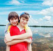 image of friendship belt  - Two teenagers on river bank against the dark blue sky - JPG