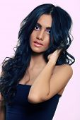 beautiful woman with long black curly hair, tanned skin and natural make-up over pink background
