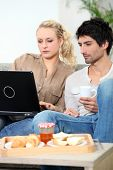Couple with laptop having breakfast