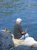 Old Man Fishing By The Sea In France