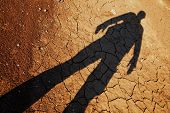 Shadow of man over cracked drought land, result of global warming poster