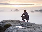 Tourist Sit On Peak Of Sandstone Rock And Watching Into Colorful Mist And Fog In  Morning Valley. Sa poster