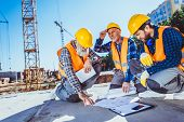 Construction Workers With Building Plans poster