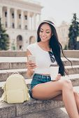 Charming Carefree Mulatto Lady Is Sitting On Stairs While On Stroll, In Jeans Short Shorts, Pause Wi poster