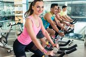 Side view of a beautiful fit young woman smiling while pedaling during cardio workout at indoor cycl poster
