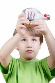 Boy in the green t-shirt looks at the miniature model of a tallship in the bottle he holds  in his a