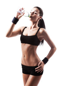 image of drinking water  - sporty muscular woman drinking water isolated against white background - JPG