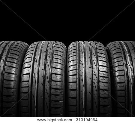 poster of Studio Shot Of A Set Of Summer Car Tires Isolated On Black Background. Tire Stack Background. Car Ty