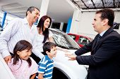 Family with a car salesman at the dealer