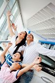 Family celebrating buying a new car with arms up