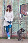 Pretty teenage girl with dog leaning against the wall on cloudy winter day