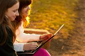 Two beautiful teenage girls having fun with notebook in the park on sunny spring day