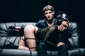 Passionate Man Sitting With Leather Spanking Paddle Near Sexy Woman In Bdsm Costume On Leather Sofa  poster