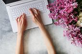 Top View Shot Of Woman Typing On White Laptop Computer, Concrete Textured Table Background. Feminine poster