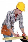 A female carpenter taking measures.
