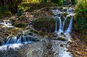 Cascade of waterfalls on the river. The small Croatian town of Slunj. The forest surround the river. poster