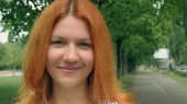 Portrait Young Cheerful Girl With Red Long Hair Outdoors In City Park. Attractive Caucasian Redhead  poster