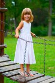 Beautiful little girl smiles while standing on the small wooden hanging bridge.