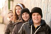 Group of smiling teenage friends posing outside on sunny winter day