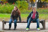 foto of puberty  - Shy boy and the girl sitting in the park and lightly touching each other finger tips - JPG