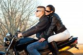 Young happy couple ready to go on a ride with motorcycle on beautiful autumn day