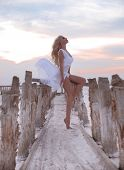 Wellness. Beautiful Free Confidence Woman In White Swimsuit Enjoy Summer Vacation At Sunset On The B poster