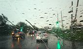 Road Traffic Of Cars On The Road Through A Front Car Wet Window With A Raindrops. poster