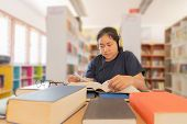 In The Library - Young Girl Student With Books Working In A High School Library. poster