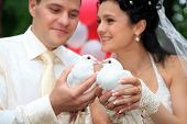 Beautiful newlyweds holding white doves in hands