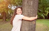 Tree Hugging, Beautiful Smiling Young Positive And Happy Environmentalist Girl Hugging The Big Tree  poster