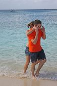 young couple playing in the surf