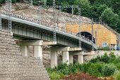 A Modern Railway Bridge Leads To A Tunnel In The Mountain. Railway In The Mountains. poster