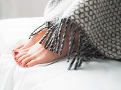 Foot Hygiene. Woman With Red Toenails Sitting On Bed, Hiding Feet Under Blanket. poster