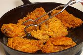 Fried Chicken Cooking In An Iron Skillet