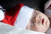 A Child Asleep Wearing A Christmas Hat