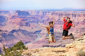 Happy people jumping in Grand Canyon. Young multiethnic couple on hiking travel. Grand Canyon, south