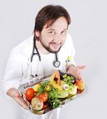 Young male doctor holding fruits and vegetables