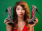 Funny young woman holding high heels shoes